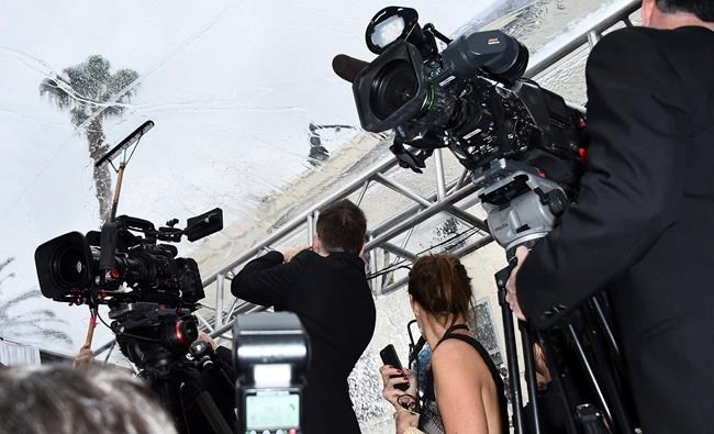 Journalists look on as rain is cleared from the red carpet at the Oscars on Sunday, Feb. 9, 2020, at the Dolby Theatre in Los Angeles. (Photo by Jordan Strauss/Invision/AP)