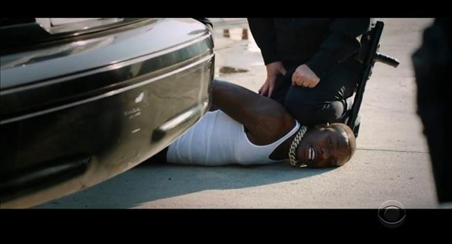 """In this video grab issued Sunday, June 28, 2020, by BET, rapper DaBaby performs """"Rockstar"""" as an actor playing a police officer presses his knee on DaBaby's neck, replicating the last few moments of George Floyd's life, during the BET Awards. (BET via AP)"""