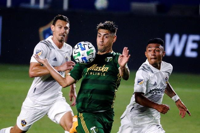 Portland Timbers forward Felipe Mora, center, controls the ball near two LA Galaxy players, including Sacha Kljestan, left, during the first half of an MLS soccer match in Carson, Calif., Wednesday, Oct. 7, 2020. (AP Photo/Ringo H.W. Chiu)