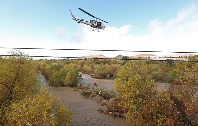 A women is hoisted out with the help of a San Bernardino County Sheriff's helicopter on Tuesday, Jan. 9, 2018, in the Santa Ana River and near the borders of Rialto, Colton, and Riverside, Calif. Three people and a dog were rescued by a helicopter after large amounts of rain fell, trapping the group at a homeless encampment in the river. (Stan Lim/Los Angeles Daily News via AP)