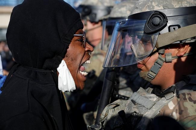 A protester yells at a member of the Minnesota National Guard Friday, May 29, 2020, in Minneapolis. Protests continued following the death of George Floyd, who died after being restrained by Minneapolis police officers on Memorial Day. (AP Photo/John Minchillo)
