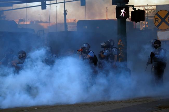 A police officer prepares to shoot tear gas Friday, May 29, 2020, in Minneapolis. Protests continued following the death of George Floyd who died after being restrained by Minneapolis police officers on Memorial Day. (AP Photo/John Minchillo)