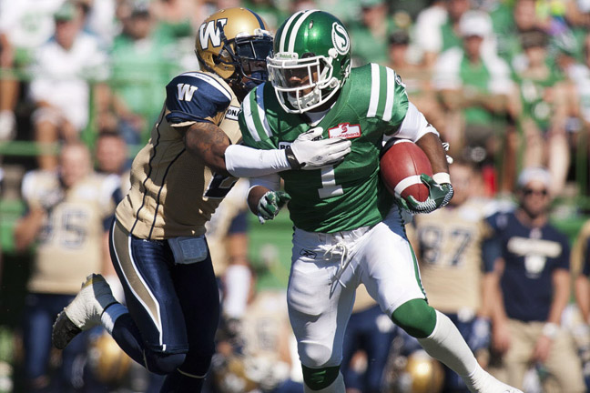 Saskatchewan Roughriders running back Kory Sheets is tackled by Winnipeg Blue Bombers corner back Jovon Johnson during the second quarter of CFL football action in Regina, Sask., Sunday.