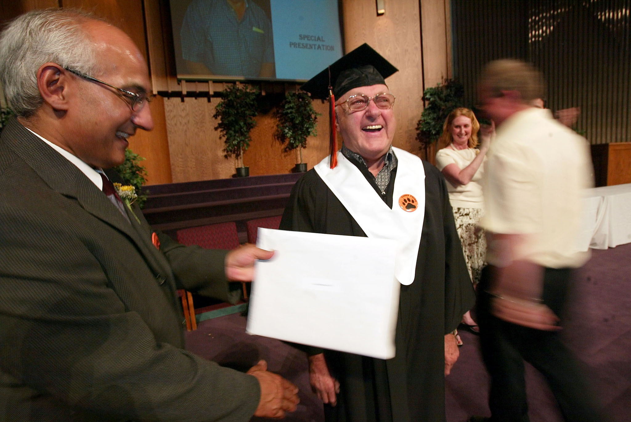 Dushant Persaud (left) surprises Barney Charach with his own diploma during a St. John's High School ceremony in 2004.