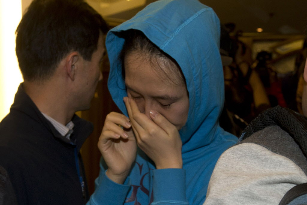 A relative of a Chinese passenger aboard the Malaysia Airlines MH370, cries after being told the latest update in Beijing, China.  (Ng Han Guan / The Associated Press)