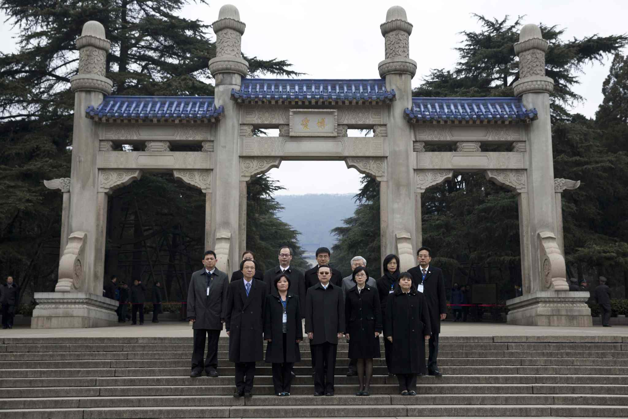 Wang Yu-chi, front centre in sun glasses, head of Taiwan's Mainland Affairs Council, poses for photos with other officials during a visit to the Mausoleum of Sun Yat-sen in Nanjing, in eastern China's Jiangsu province on Wednesday, Feb. 12, 2014. China and Taiwan hailed a new chapter in their relations on Tuesday and said their ties would advance after they held their highest-level government talks since they split amid civil war in 1949.