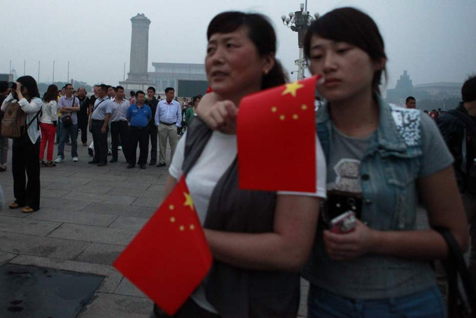 Tourists gather for the flag raising ceremony on Tiananmen Square to mark the anniversary of the deadly 1989 crackdown on pro-democracy protestors, in Beijing, China. (AP Photo/Ng Han Guan)