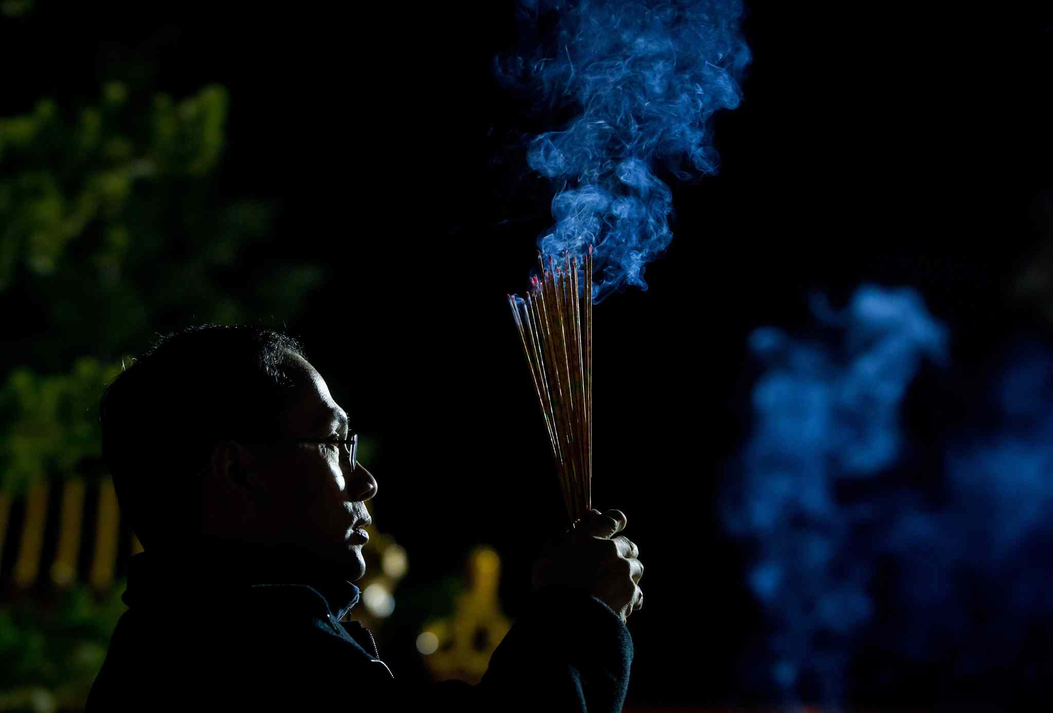 A man burns incense sticks and prays to mark the Lunar New Year at the International Buddhist Temple in Richmond, B.C., late Thursday, January 30, 2014. Thousands of people gathered at the temple to celebrate the beginning of the new year.