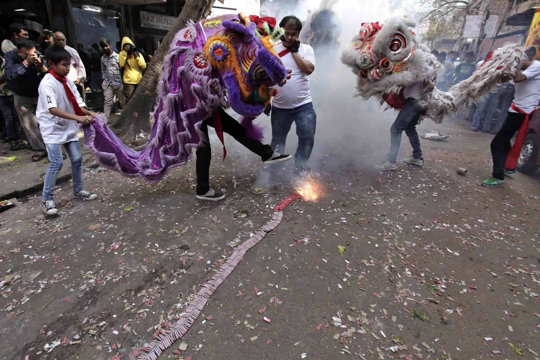 Chinese Lion dancers perform amid exploding fire crackers during Chinese New Year celebrations in Kolkata, India on Friday, Jan. 31, 2014.