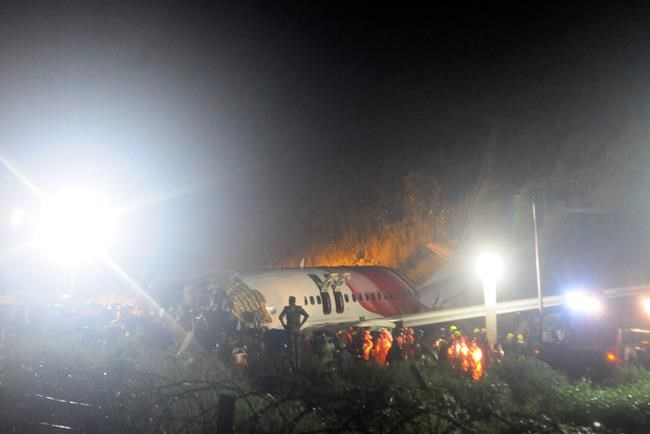 The Air India Express flight that skidded off a runway while landing at the airport in Kozhikode, Kerala state, India, Friday, Aug. 7, 2020. The special evacuation flight bringing people home to India who had been trapped abroad because of the coronavirus skidded off the runway and split in two while landing in heavy rain killing more than a dozen people and injuring dozens more. (AP Photo/C.K.Thanseer)