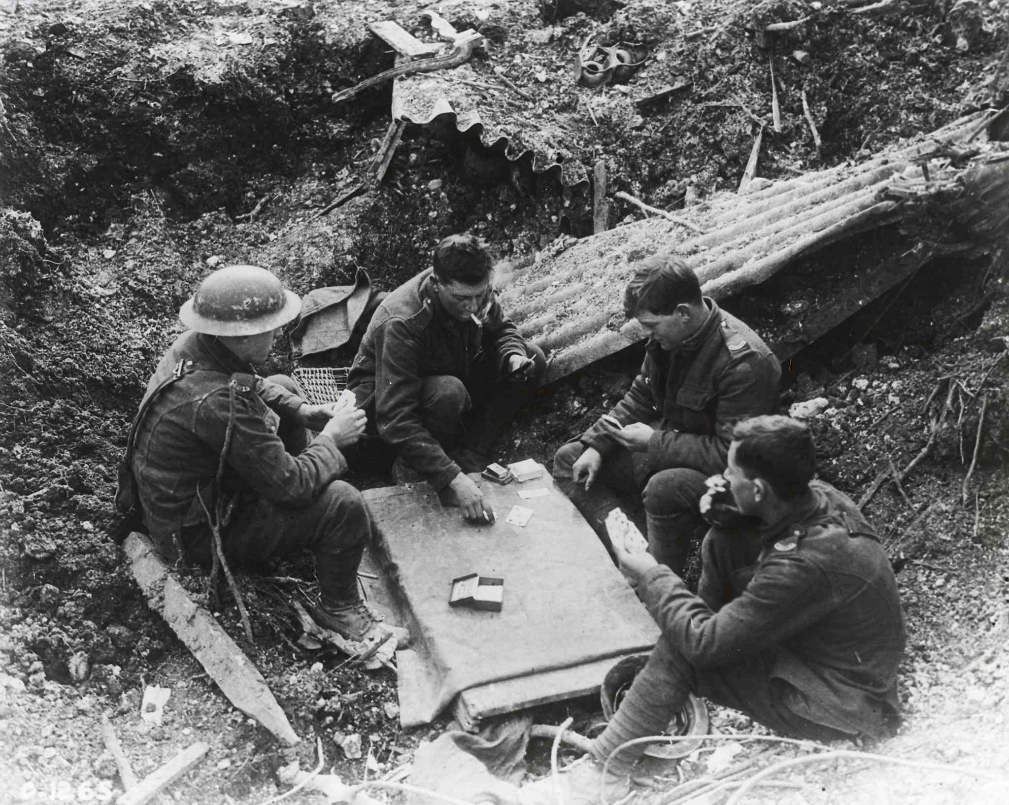 Canadians play a game of cards in a shell hole in 1917.