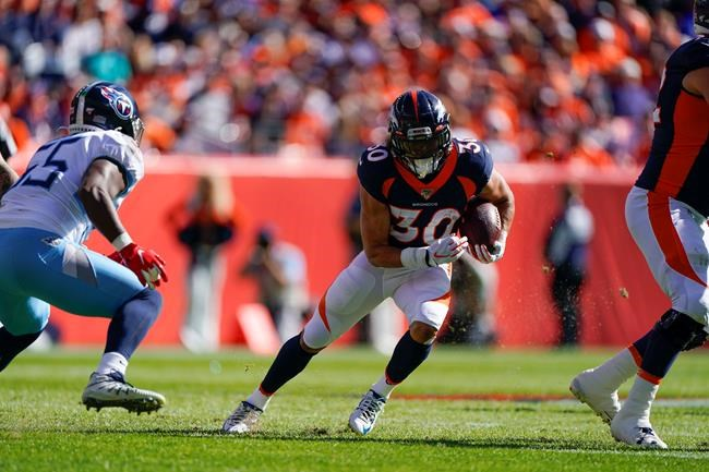Denver Broncos running back Phillip Lindsay, center, runs with the ball during the first half of an NFL football game against the Tennessee Titans, Sunday, Oct. 13, 2019, in Denver. (AP Photo/Jack Dempsey)