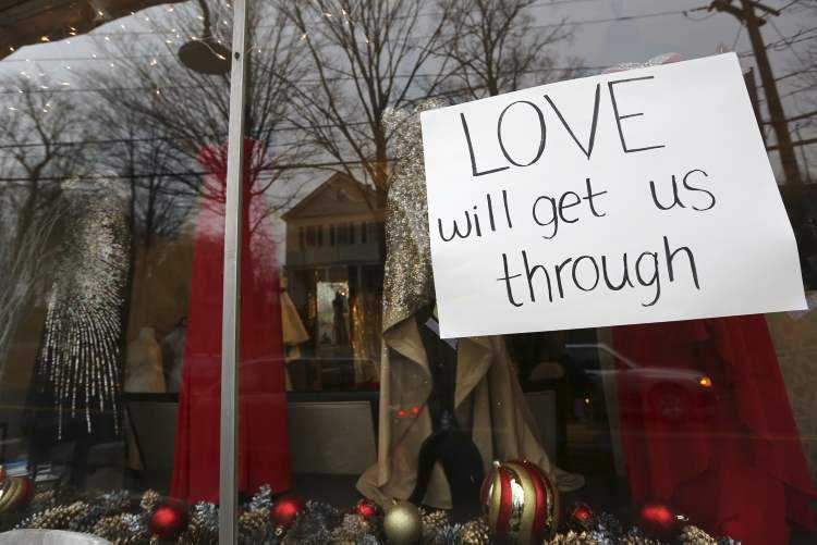 A sign hangs in the window of a clothing store Sunday, in Newtown, Conn. On Friday, a gunman allegedly killed his mother at their home and then opened fire inside the Sandy Hook Elementary School, killing 26 people, including 20 children. (AP Photo/Mary Altaffer)