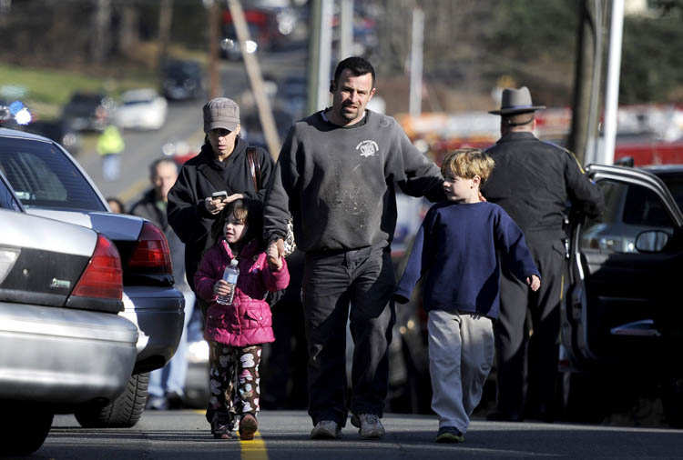 Parents leave a staging area after being reunited with their children following a shooting at the Sandy Hook Elementary School in Newtown, Conn., about 60 miles (96 kilometers) northeast of New York City, Friday, Dec. 14, 2012. An official with knowledge of Friday's shooting said 27 people were dead, including 18 children. It was the worst school shooting in the country's history. (Jessica Hill / The Associated Press)