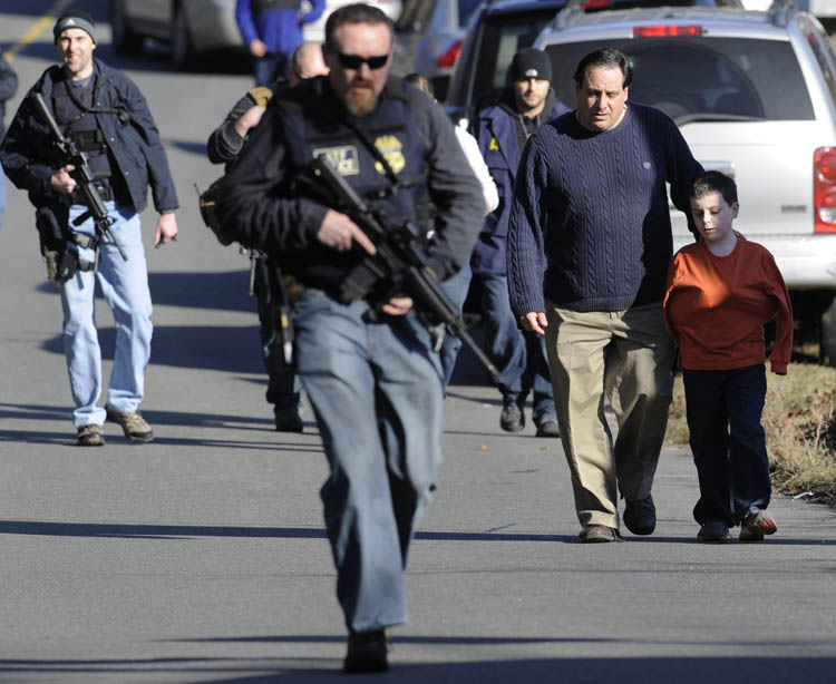 Parents leave a staging area after being reunited with their children following a shooting at the Sandy Hook Elementary School in Newtown, Conn., about 60 miles (96 kilometers) northeast of New York City, Friday, Dec. 14, 2012. An official with knowledge of Friday's shooting said 27 people were dead, including 18 children.