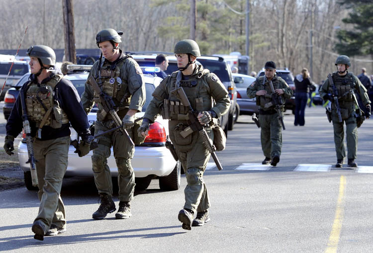 State Police are on scene following a shooting at the Sandy Hook Elementary School in Newtown, Conn., about 60 miles (96 kilometers) northeast of New York City, Friday, Dec. 14, 2012. An official with knowledge of Friday's shooting said 27 people were dead, including 18 children. (Jessica Hill / The Associated Press)