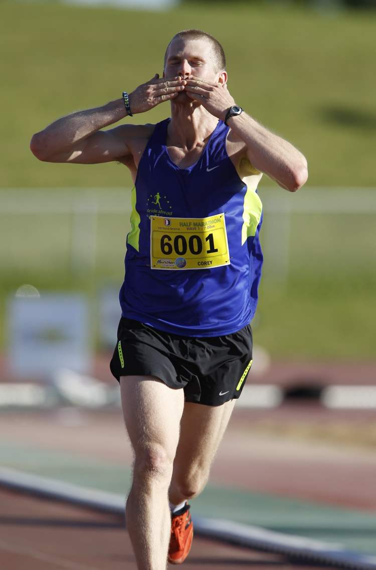 Corey Gallagher salutes the crowd in University Stadium as he wins the half-marathon with a time of 1:10:50, at the 35th Manitoba Marathon Sunday.