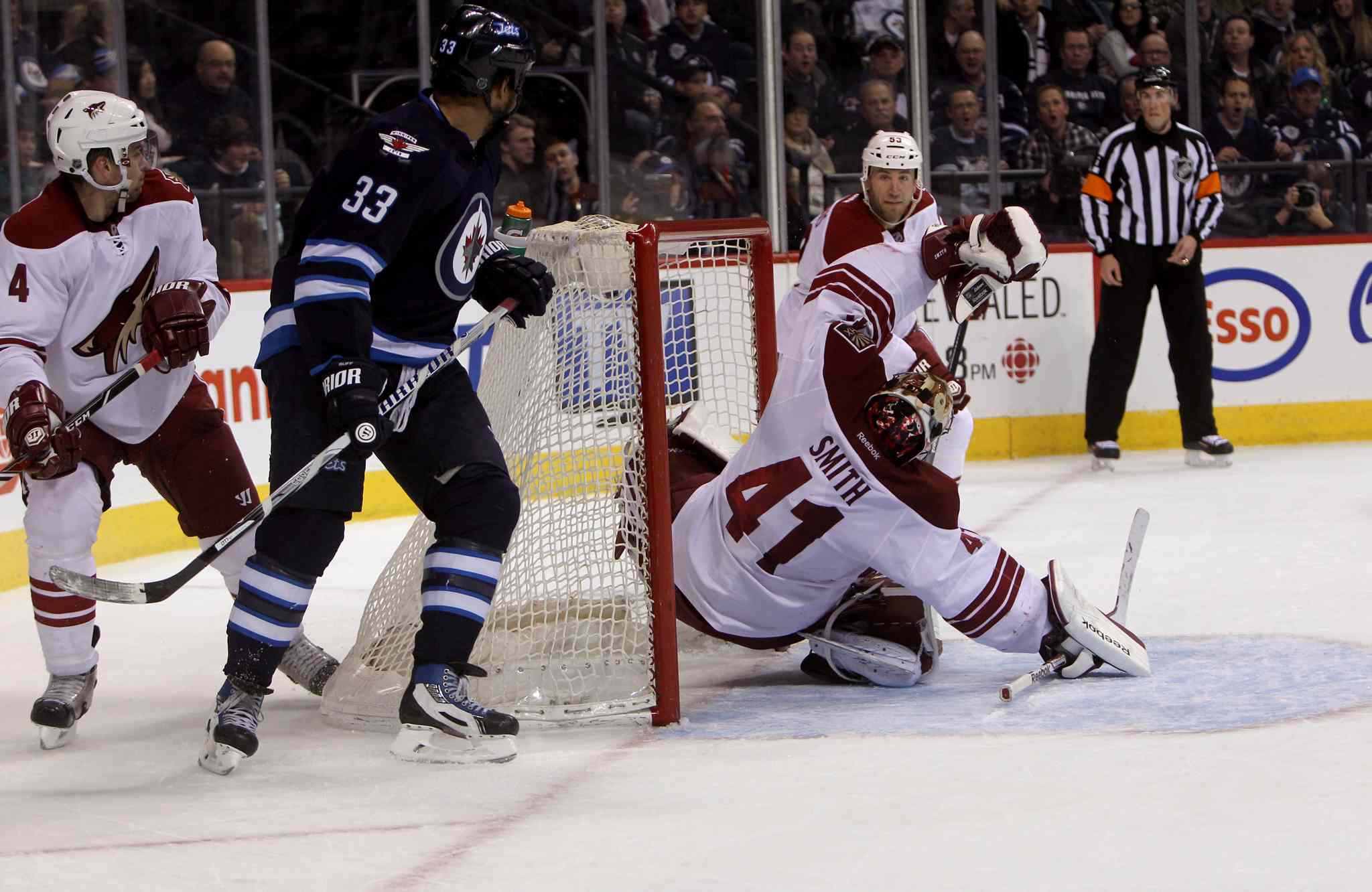 Phoenix Coyotes' goalie Mike Smith (41) trips after Winnipeg Jets' Bryan Little's (18) unassisted second-period shot sails past him.