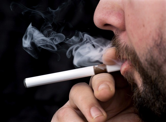 A smoker puffs on an electronic cigarette in Halifax on Friday, Feb. 7, 2014. Designed to simulate smoking, electronic cigarettes continue to grow in popularity but uncertainty over possible Health Canada regulations and restrictions by other regulators are raising concerns for the industry in Canada. THE CANADIAN PRESS/Andrew Vaughan
