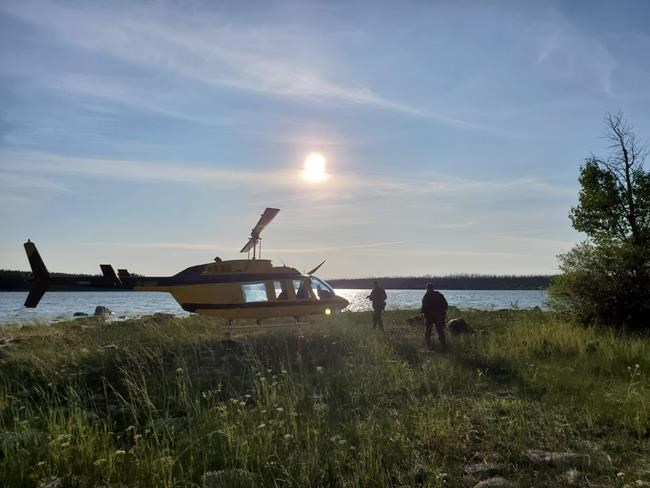 Officers look through a remote lake area alongside a landed helicopter in the Gillam, Man., area in July 28, 2019, police image published to social media. THE CANADIAN PRESS/HO-Twitter, Royal Canadian Mounted Police, @rcmpmb, *MANDATORY CREDIT*
