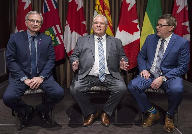 Ontario Premier Doug Ford, centre, speaks to reporters as Saskatchewan Premier Scott Moe, right, and New Brunswick Premier Blaine Higgs look on during a meeting of Canada's premiers in Montreal, Thursday, December 6, 2018. Three of Canada's premiers will announce they'll fight climate change by working together on small nuclear reactors, a company that's developing the technology says. THE CANADIAN PRESS/Graham Hughes