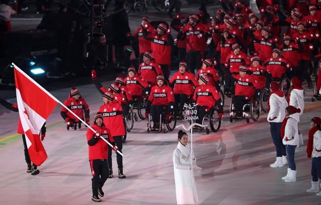 Brian McKeever carries the flag of Canada as he leads his teammates into the opening ceremony of the 2018 Winter Paralympics in Pyeongchang, South Korea, Friday, March 9, 2018. McKeever has become the most decorated winter Paralympian in Canadian history.THE CANADIAN PRESS/AP/Ng Han Guan