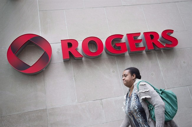 A pedestrian walks past the Rogers Building in Toronto on Tuesday, April 22, 2014. Rogers Communications Inc. will issue its first-quarter results Monday, shedding light on whether the telecom company continues to grapple with a defection of wireless subscribers to competitors. THE CANADIAN PRESS/Darren Calabrese