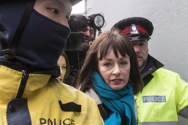 Lucy DeCoutere leaves the Toronto courthouse escorted by police following the reading of the verdict in the Jian Ghomeshi sexual assault trial on Thursday, March 24, 2016. One of three women who accused Jian Ghomeshi of sexual assault outside his workplace says they were never given the option of seeking a peace bond instead of testifying during the radio celebrity's two-week trial earlier this year. THE CANADIAN PRESS/Chris Young