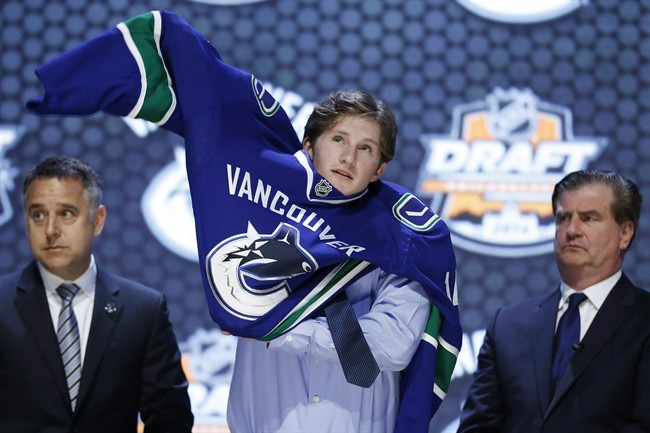 Jared McCann pulls on a Vancouver Canucks sweater after being chosen 24th overall during the first round of the NHL hockey draft, Friday, June 27, 2014, in Philadelphia. The Canucks have signed McCann to an entry-level contract. THE CANADIAN PRESS/AP/Matt Slocum