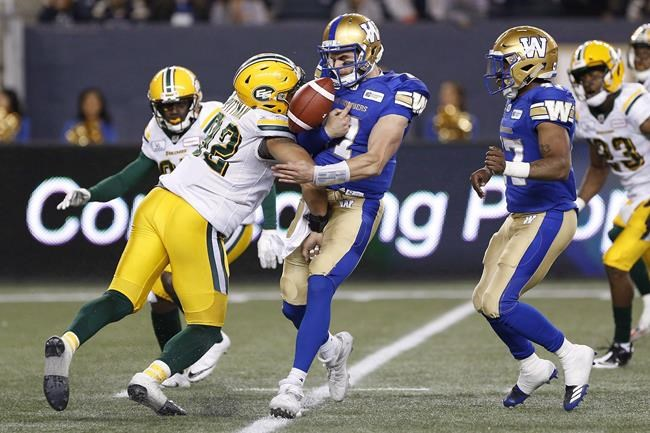 Winnipeg Blue Bombers quarterback Chris Streveler (17) fumbles the ball after getting hit by Edmonton Eskimos' Brandon Pittman (92) during the second half of pre-season CFL action in Winnipeg Friday, June 1, 2018. For the first time since 1994, a true rookie quarterback will start a CFL regular-season game. Chris Streveler will take snaps for the Winnipeg Blue Bombers when they open the '18 season against the Edmonton Eskimos. THE CANADIAN PRESS/John Woods