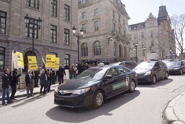 Taxi drivers demonstrate outside the premier's office as the cabinet meets at the Quebec legislature, in Quebec City on Wednesday, May 4, 2016. The head of a taxi lobby in Quebec says ride-hailing company Uber has the attitude of a hardened criminal.THE CANADIAN PRESS/Jacques Boissinot