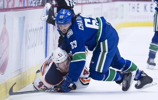 Vancouver Canucks defenceman Jalen Chatfield puts Edmonton Oilers right wing Josh Currie (43) into the boards during first period NHL preseason action in Vancouver on September, 17, 2019. Jalen Chatfield is poised to make his NHL debut with the Vancouver Canucks after the club recalled the defenceman from their American Hockey League affiliate in Utica, N.Y. THE CANADIAN PRESS/Jonathan Hayward