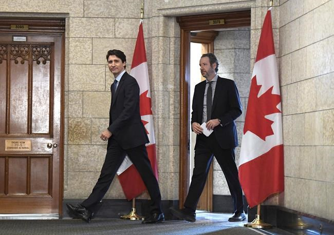 Prime Minister Justin Trudeau leaves his office with his principal secretary Gerald Butts to attend an emergency cabinet meeting on Parliament Hill in Ottawa on Tuesday, April 10, 2018. Butts has resigned amid allegations that the Prime Minister's Office interfered to prevent criminal prosecution of SNC-Lavalin. THE CANADIAN PRESS/Justin Tang