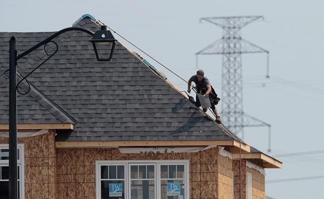 "A construction worker shingles the roof of a new home in a development in Ottawa on Monday, July 6, 2015. Canada's national housing agency says the 47 per cent decline in the country's insured mortgage market year-over-year in the third quarter is the ""new normal level."" THE CANADIAN PRESS/Sean Kilpatrick"