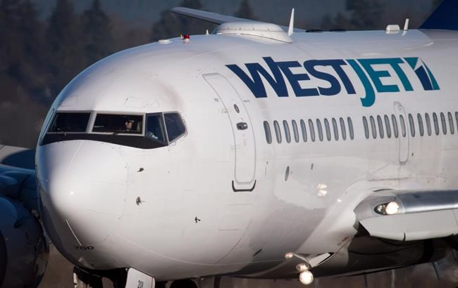 A pilot taxis a Westjet Boeing 737-700 plane to a gate after arriving at Vancouver International Airport in Richmond, B.C., on Monday February 3, 2014. The proposed acquisition of WestJet Airlines by Onex Corp. moved a step closer to completion after Canada's transportation regulator determined the airline will continue to meet Canadian ownership and control requirements. THE CANADIAN PRESS/Darryl Dyck
