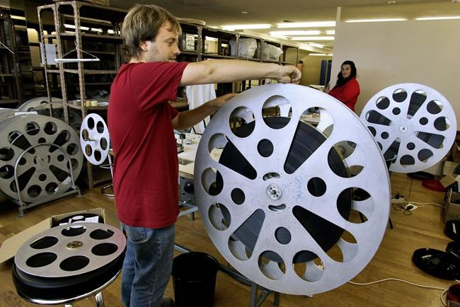 A worker prepares a movie reel at the 53rd San Sebastian Film Festival Cinema in San Sebastian nothern Spain, Wednesday, Sept. 15, 2005. Women are making some headway towards gender parity in Canadian film and TV production, but a new report says progress isn't being shared across the board. THE CANADIAN PRESS/AP Photo/Alvaro Barrientos