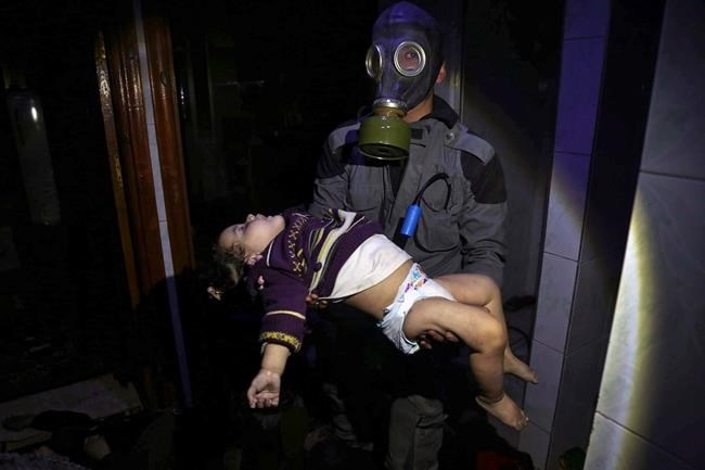 EDS NOTE: GRAPHIC CONTENT - This image released early Sunday, April 8, 2018 by the Syrian Civil Defense White Helmets, shows a rescue worker carrying a child following an alleged chemical weapons attack in the rebel-held town of Douma, near Damascus, Syria. Canada has become the latest to lay the blame for a deadly chemical-weapons attack in Syria last week at Syrian President Bashar al-Assad's doorstep, despite Russian suggestions to the contrary. THE CANADIAN PRESS/Syrian Civil Defense White Helmets via AP