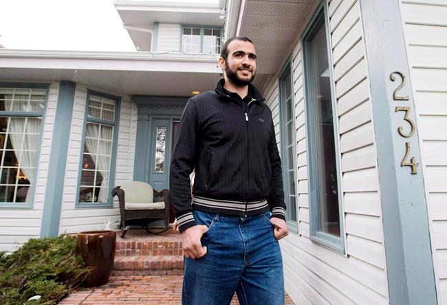 Omar Khadr walks out the front door of his lawyer Dennis Edney's home to speak the media in Edmonton, Thursday, May 7, 2015. Former Guantanamo Bay detainee Omar Khadr is back in court today to seek changes to bail conditions imposed while he appeals war crime convictions by a U.S. military commission. THE CANADIAN PRESS/Nathan Denette
