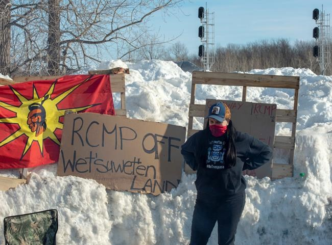 A member of the Mohawk community stands near the blockade of the commuter rail line in Kahnawake, Quebec. (Ryan Remiorz / Canadian Press)