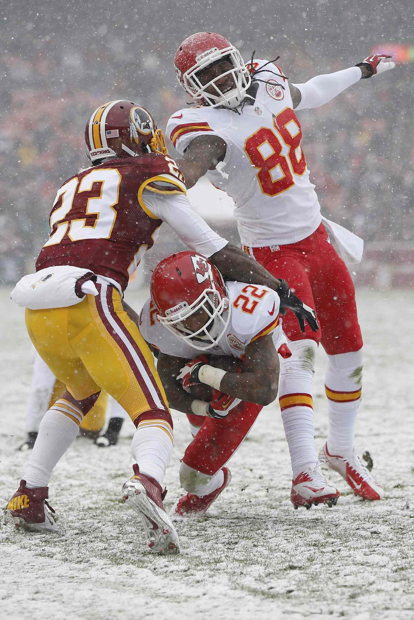 Kansas City Chiefs wide receiver Dexter McCluster (bottom) slides between Washington Redskins cornerback DeAngelo Hall (left) and wide receiver Junior Hemingway (88) during the first half of an NFL football game in Landover, Md. on Sunday.