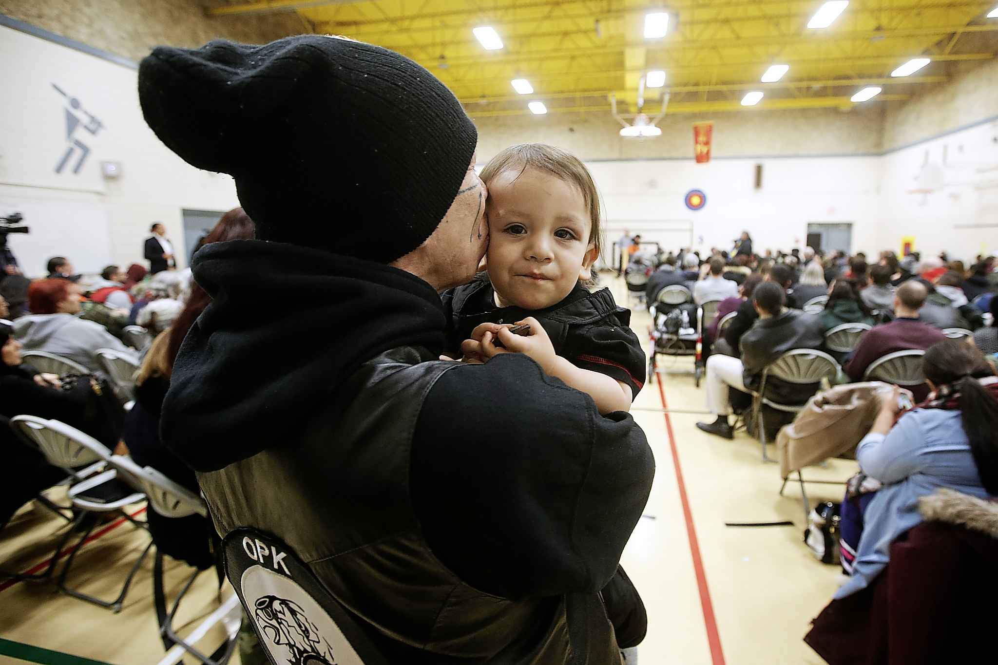 A young boy gets a kiss from his father at a community gathering organized to talk about community issues at William Whyte School.