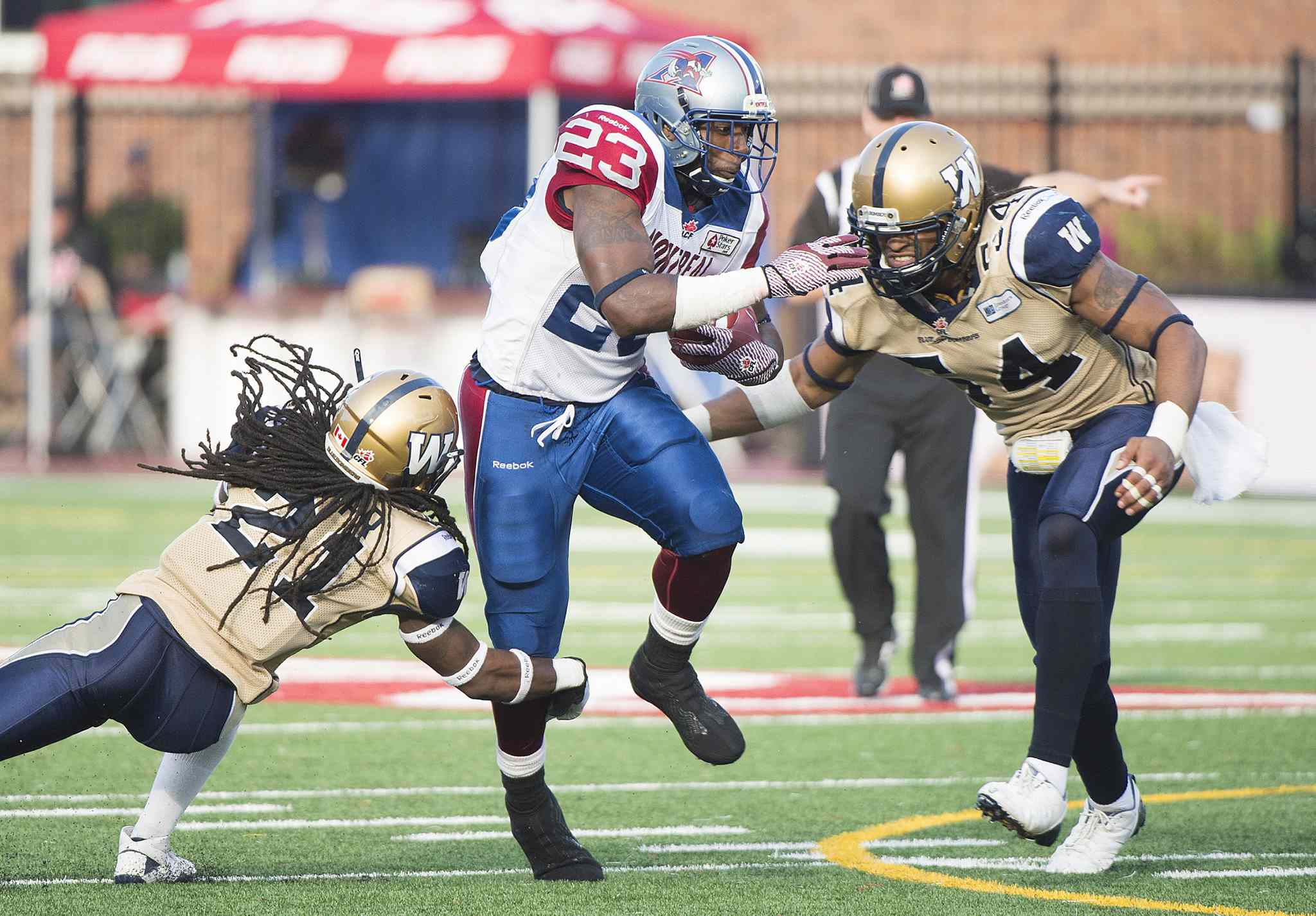 Winnipeg Blue Bombers' Alex Suber, left, and Kenny Mainor, right, tackle Montreal Alouettes' Jerome Messam during second half CFL football action in Montreal Monday.