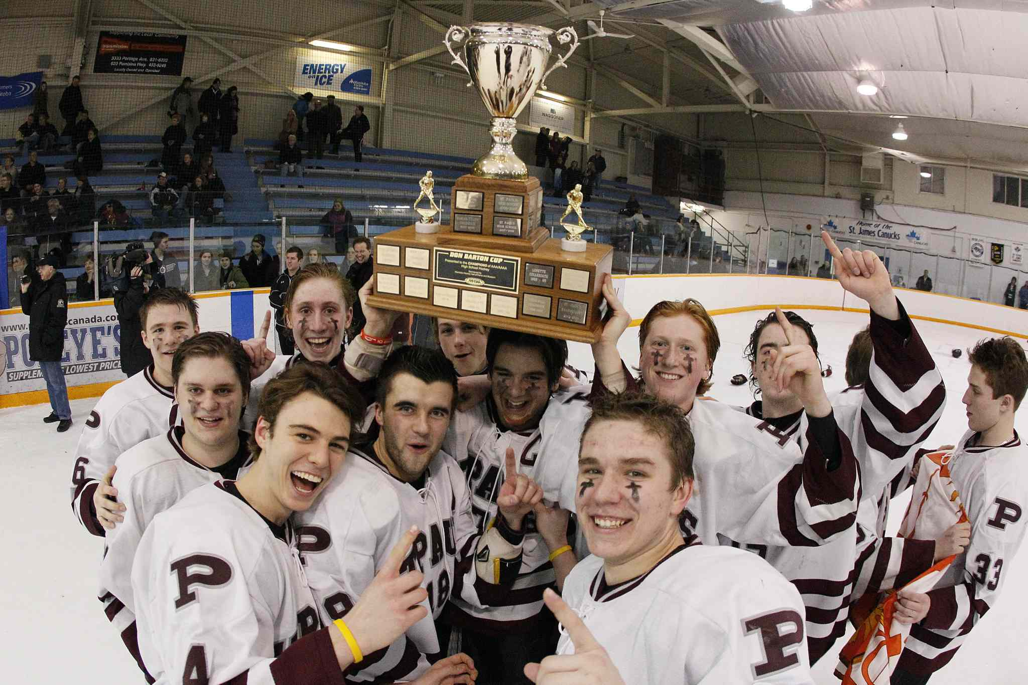 Members of the St. Paul's Crusaders celebrate a 4-1 win over the River East Kodiaks in the AAAA Provincial High School Hockey Championship at St. James Civic Centre Monday night.