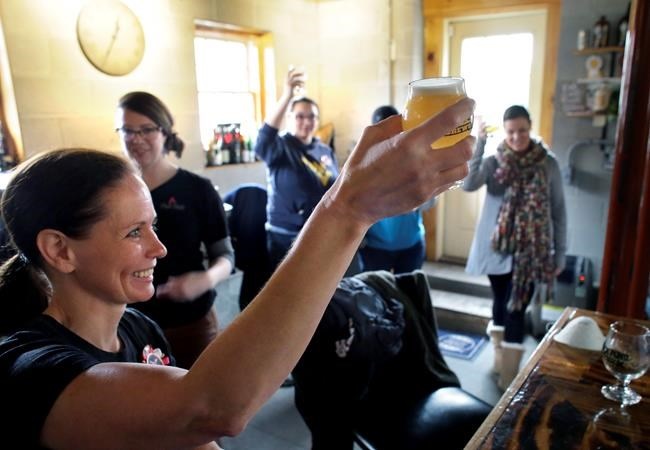In this Sunday, March 4, 2018, photo, Elizabeth Bove, of Woodstock, Conn., left, joins with others as they raise their glasses in a toast after helping brew a batch of beer at Black Pond Brews brewery, in Danielson, Conn. The brewery hosted homebrewers and beer enthusiasts for a Pink Boots Society event in honor of International Women's Day, on March 8. Thousands of women in the beer business and homebrewers in a number of countries are brewing together around that day as a way to raise the profile of women in a male-dominated industry. (AP Photo/Steven Senne)