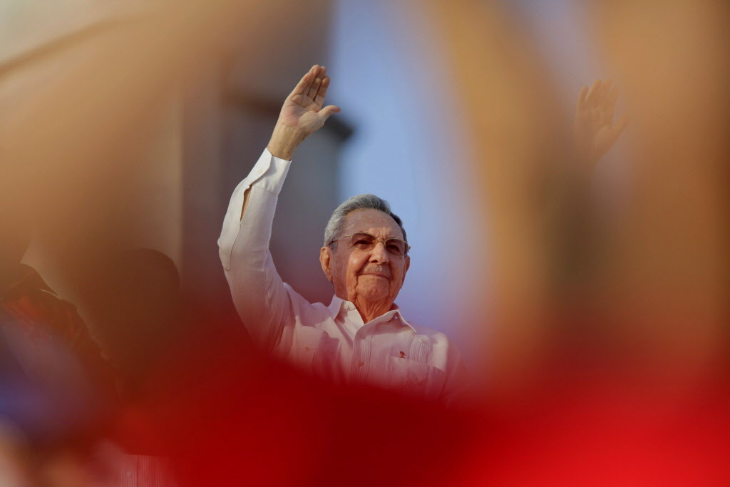 Cuba's President Raul Castro waves to workers as he watches the May Day march in Havana. Cuba marks each May Day not with protests but with massive marches organized by workplaces, schools and government. Thousands of islanders filed through Havana's Revolution Plaza on Thursday to a soundtrack of congas, drums and cries of