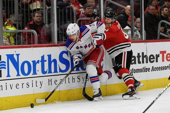 New York Rangers' Tony DeAngelo (77) battles Chicago Blackhawks' Dominik Kubalik (8) of The Czech Republic, for a loose puck during the first period of an NHL hockey game Wednesday, Feb. 19, 2020, in Chicago. (AP Photo/Paul Beaty)