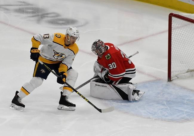 Chicago Blackhawks goaltender Cam Ward (30) makes a save on Nashville Predators center Nick Bonino (13) during the first period of an NHL hockey game Tuesday, Dec. 18, 2018, in Chicago. (AP Photo/David Banks)