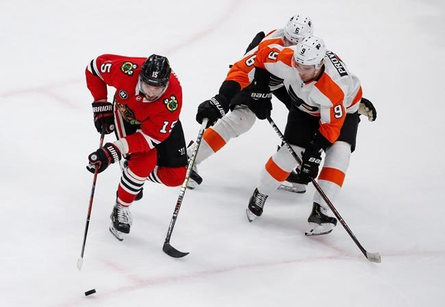 Chicago Blackhawks center Artem Anisimov (15) keeps the puck away from Philadelphia Flyers defenseman Ivan Provorov (9) and defenseman Travis Sanheim (6) during the second period of an NHL hockey game Thursday, March 21, 2019, in Chicago. (AP Photo/Kamil Krzaczynski)