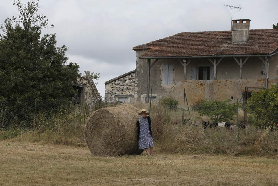 An elderly woman on a farm watches the pack go by during the 18th stage of the Tour de France. (AP Photo/Christophe Ena)