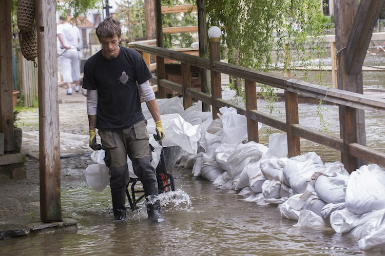A young man delivers sandbags along the swollen Vltava river in Cesky Krumlov, about 170 km south of Prague in the Czech Republic.